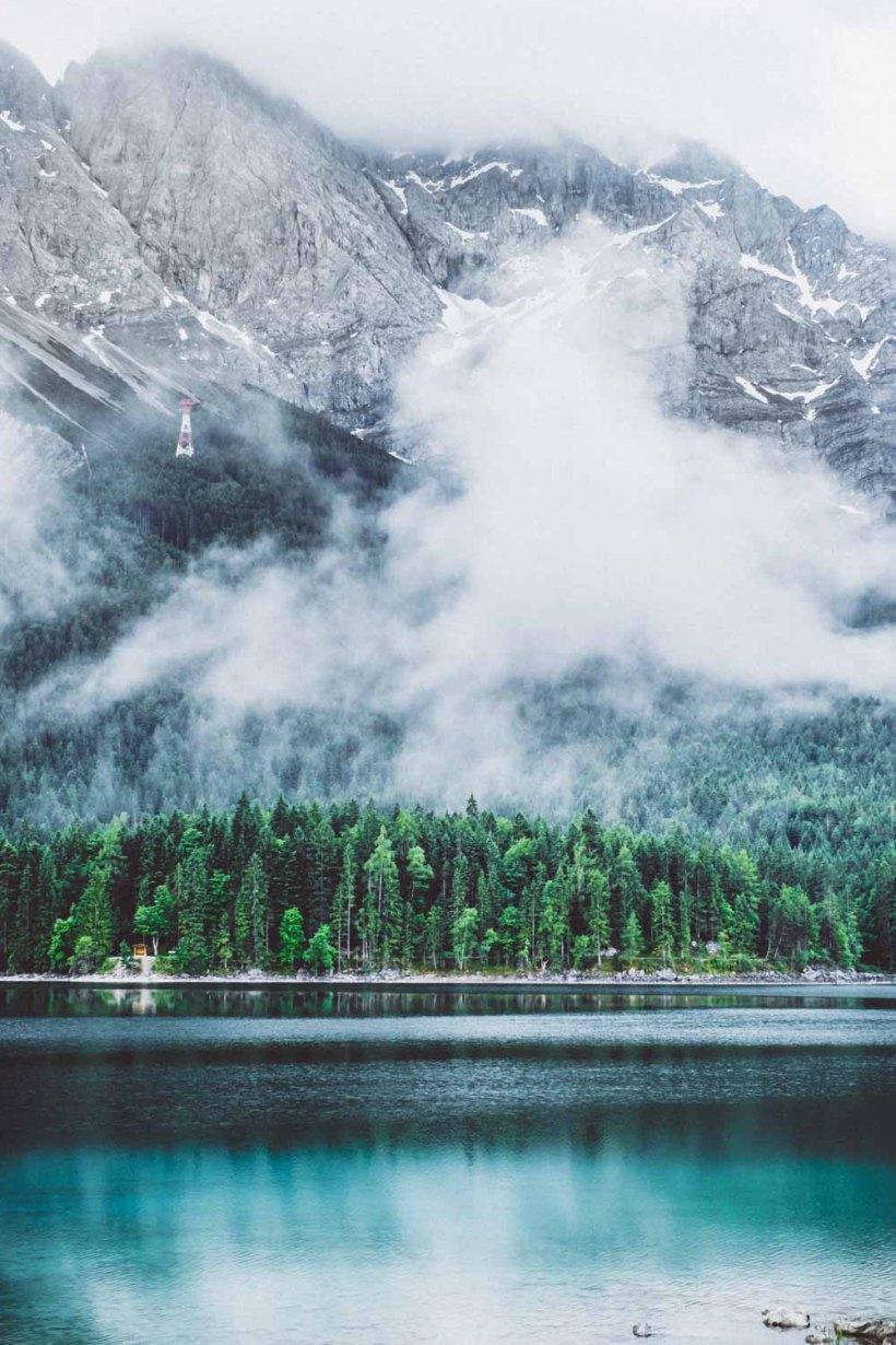 Wolken schieben sich langsam über den See und die Hänge entlang