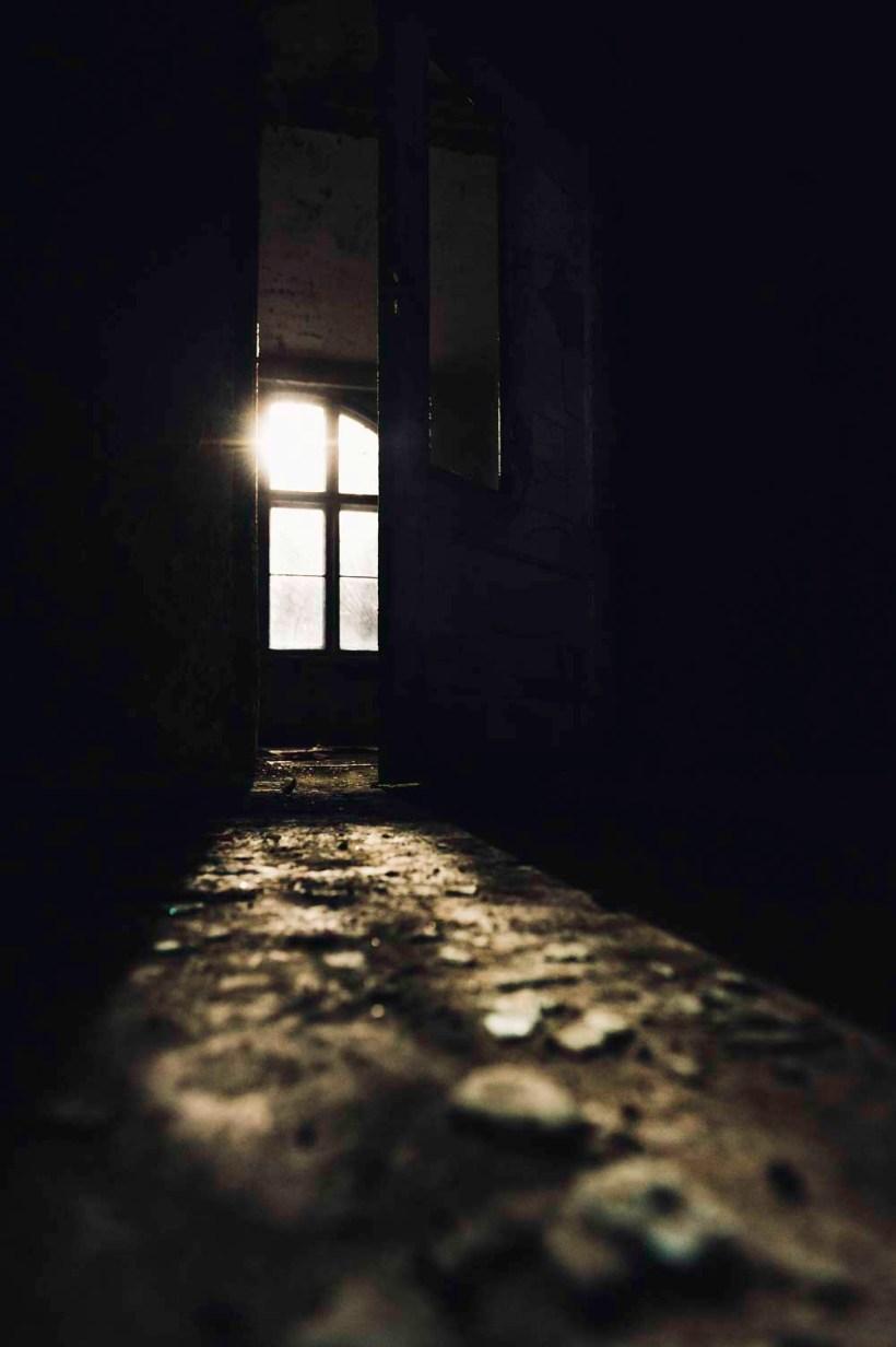 Glassplitter liegen auf dem Boden. Die Sonne scheint durch eine offen stehende Tür in den Hauptgang.