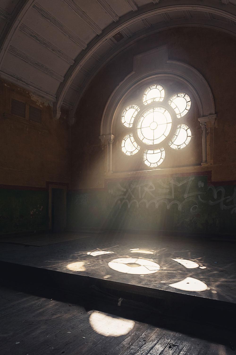 Licht fällt durch das große Rosettenfenster am Ende des Saales. Die Stimmung wurde mit Photoshop noch etwas verstärkt.