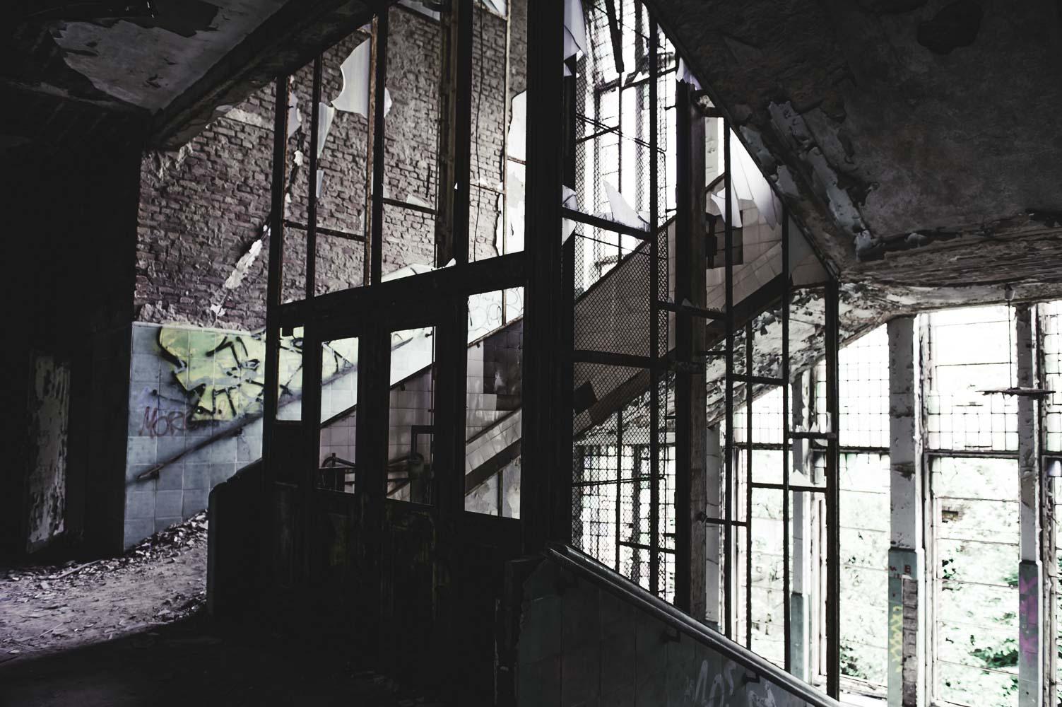 Die helle und breite Haupttreppe ist fast vollständig mit Putz von den Wänden und der Decke bedeckt.