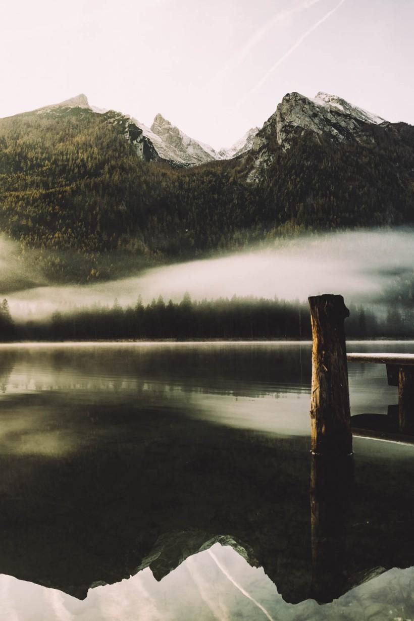 """Das Gebirge spiegelt sich in der glatten Wasseroberfläche. Nur ein Holzpfahl """"durchbricht"""" die Ruhe."""