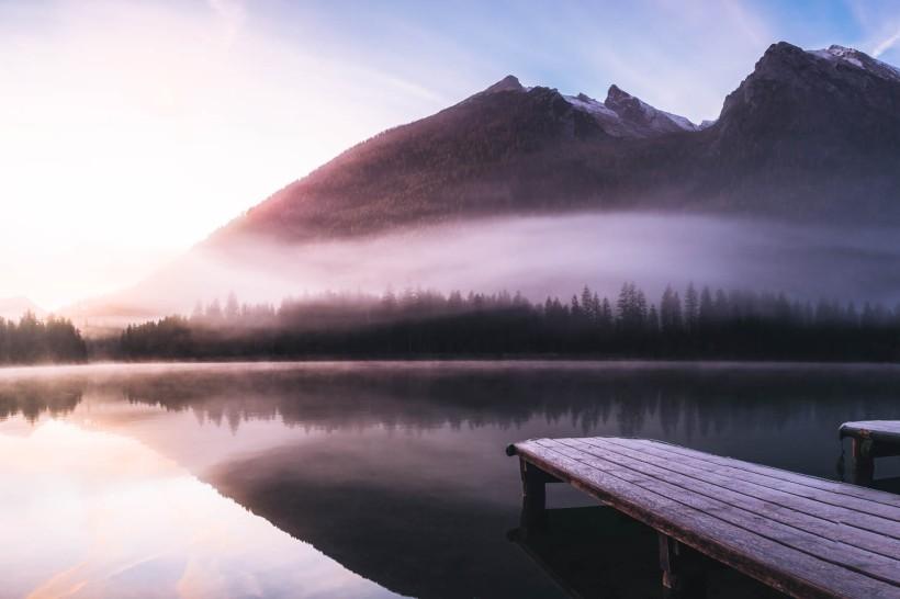 Die Bootsstege ragen in den Hintersee. Im Hintergrund ragen die Gipfel des Hochkaltermassivs in den Morgenhimmel.