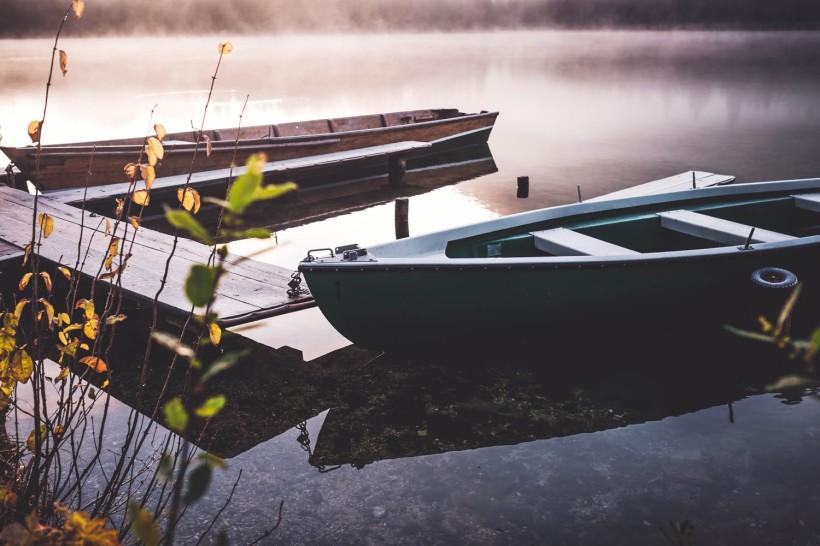 Die letzten Boote liegen ruhig und festgemacht am Seeufer. Das Wasser um sie herum scheint glatt wie ein Spiegel.