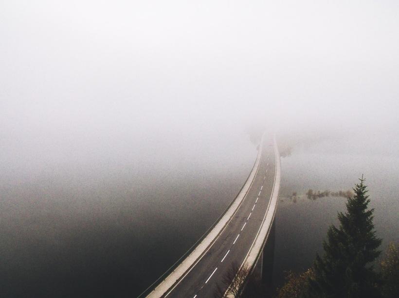 Die Straße verschwindet in den tiefhängenden Wolken. Das andere Ufer des Sylvensteinsees ist kaum zu erkennen.