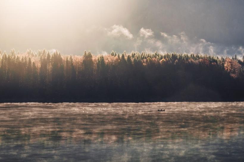 Bildunterschrift: Die Sonne taucht die Wälder rund um den See in weiches und kräftiges Licht. Nebelschwaden steigen immer noch aus den Wäldern auf.