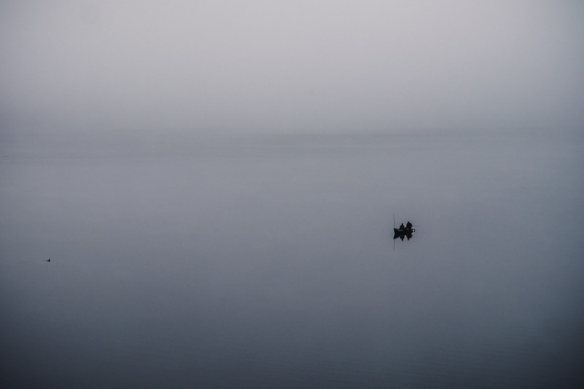 Angler nutzen die morgendliche Ruhe. Sie umhüllt vom Nebel der Wolken.
