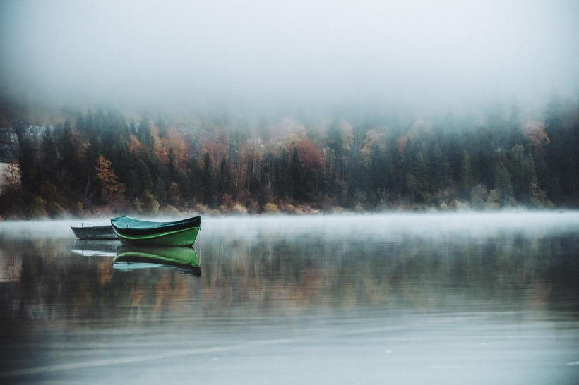 Einige Boote lagen ruhig und festgemacht am Ufer des Sees. Sie spiegelten sich perfekt im glatten Wasser.