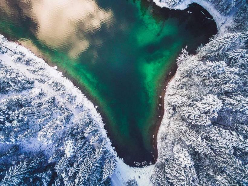 Der Eibsee im Winter. Das typische türkise Wasser bildet einen tollen Kontrast zum verschneiten Wald.