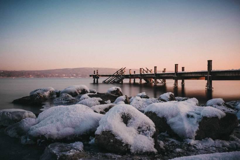 Das mit Schnee bedeckte Ufer und ein Steg ragen in den Starnberger See.