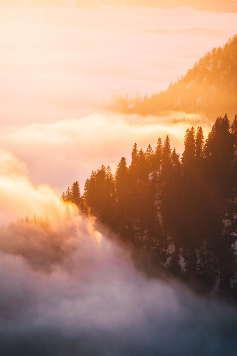 Das warme Licht der aufgehenden Sonne streift die Wälder an den Berghängen und taucht sie in warmes Licht.