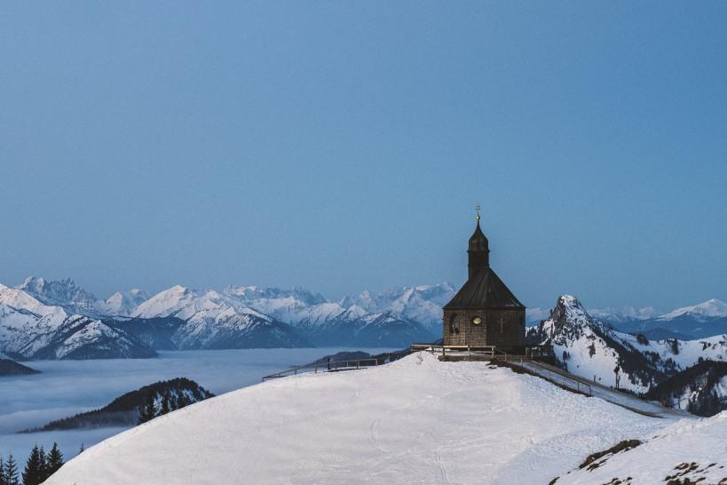 Die Kapelle am Wallberg im ersten faden Licht des Tages. Das Tal liegt unter einer dicken Wolkendecke.