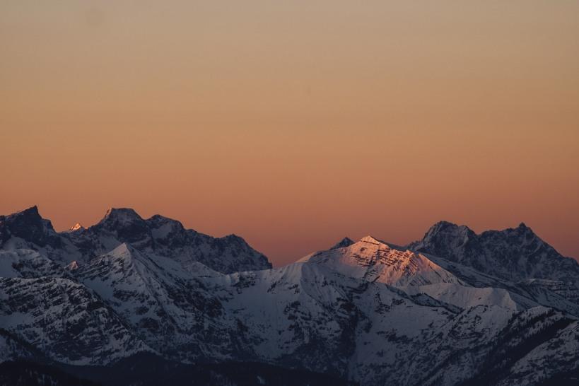 Das erste Sonnenlicht erhellt die umliegenden Gipfel.