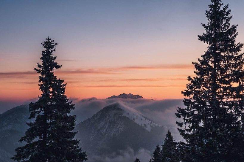 Die Wolken lösten sich langsam im Licht der aufgehenden Sonne auf und krochen über den Gipfel des Jochbergs.