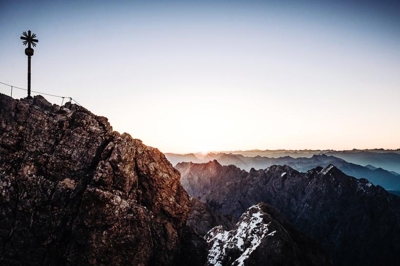 Im Juni geht es hoch hinaus. Das Motiv zeigt den Sonnenaufgang auf der Zugspitze und die Sonne wie gerade über die Gipfel der Alpen steigt.