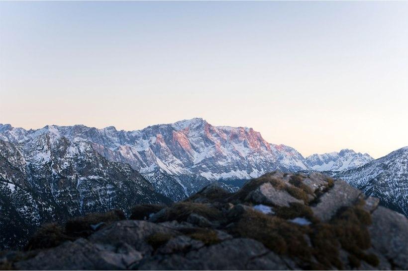 die schneebedeckte zugspitze im Abendrot mit verschwommenen steinen im vordergrund