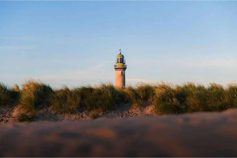 blick durch die dünen zum leuchtturm von warnemünde